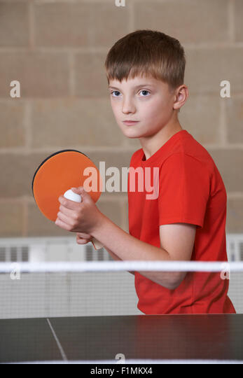 Boy Playing Table Tennis In School Gym - Stock Image