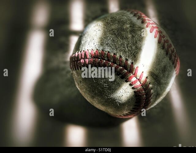 Detail of an old weathered baseball on a bench - Stock Image