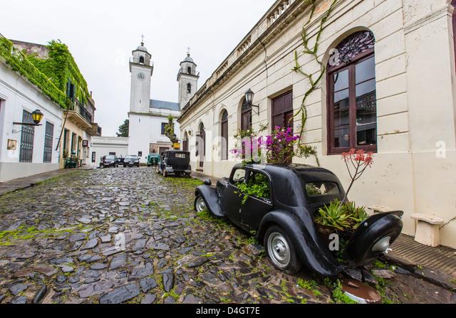 Old car turned into planter on cobblestone street in Colonia del Sacramento, Uruguay, South America - Stock Image