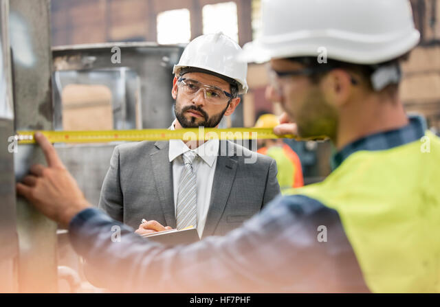 Manager watching steel worker with tape measure in factory - Stock Image