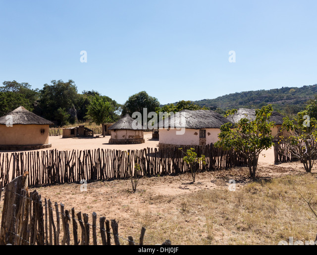 View of thatched mud homes in typical African village in Zimbabwe, Africa - Stock Image