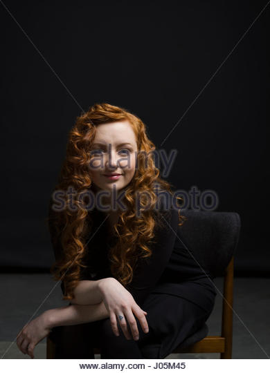 Portrait confident woman with curly red hair against black background - Stock Image
