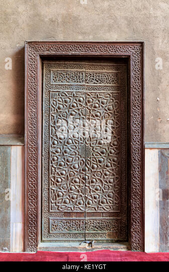 Closed wooden aged door with ornate bronzed geometric patterns at Sultan Hassan Mosque, Cairo, Egypt - Stock Image