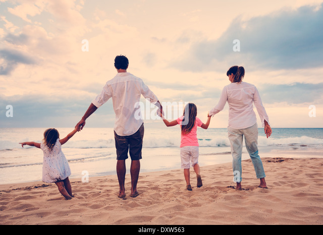 Happy Young Family Having Fun on Beach at Sunset - Stock Image