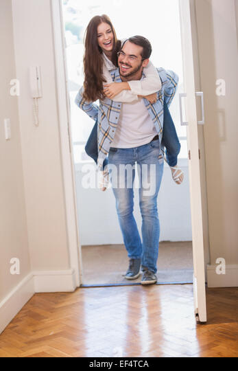 Young man giving girlfriend a piggyback ride - Stock Image