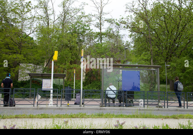 Teenagers waiting bus at a bus stop after school - Stock-Bilder