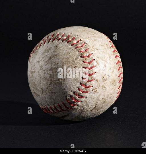 Old leather baseball on black background - Stock Image