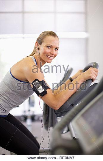 Woman on exercise bike - Stock Image