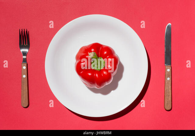 Top view of red bell pepper on white plate with knife and fork on red background - Stock Image