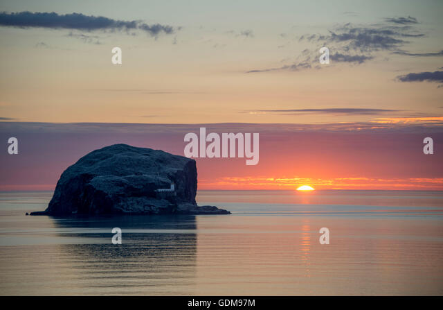 Bass Rock, Scotland, UK. 19th July, 2016. UK weather. The sun rises behind The Bass Rock 1.2 miles off the the East - Stock Image