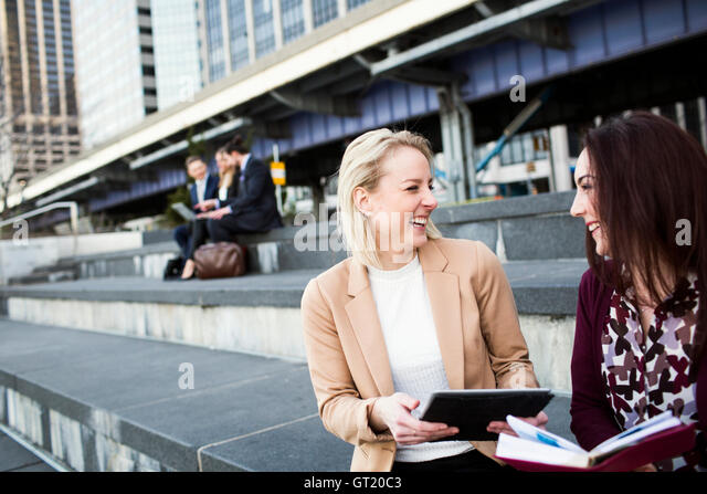 Happy colleagues with digital tablet with business people discussing in background - Stock-Bilder