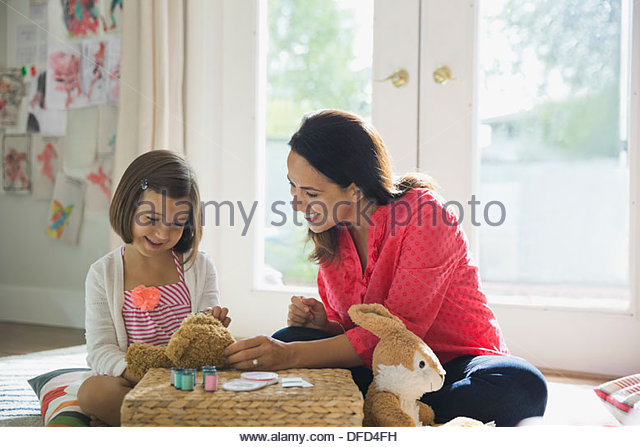 Mother and daughter repairing stuffed animals at home - Stock Image