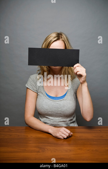 A young woman holding a censorship strip in front of her face - Stock Image
