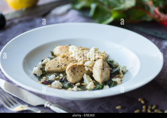 Lemon Chicken with Sauteed Chard and Pine Nuts - Stock Image