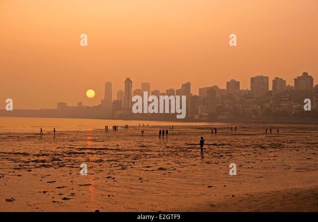 India Maharashtra state Mumbai Chowpatty beach sunset with red sun coming down under skyline - Stock Image