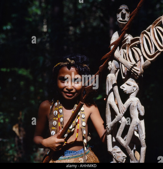 INDONESIA Southeast Asia Irian Jaya Sorong Young girl beside traditional wooden carvings. - Stock Image