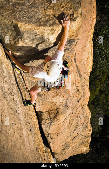 A rock climber reaches for the top on a sandstone crag in Santa Barbara. - Stock Image