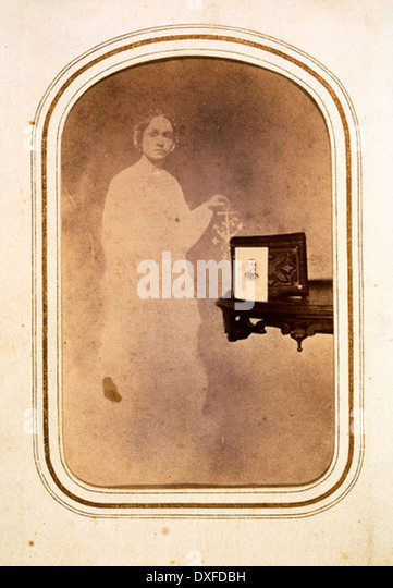 Spirit Photograph [Woman's spirit behind table with photograph] - Stock-Bilder