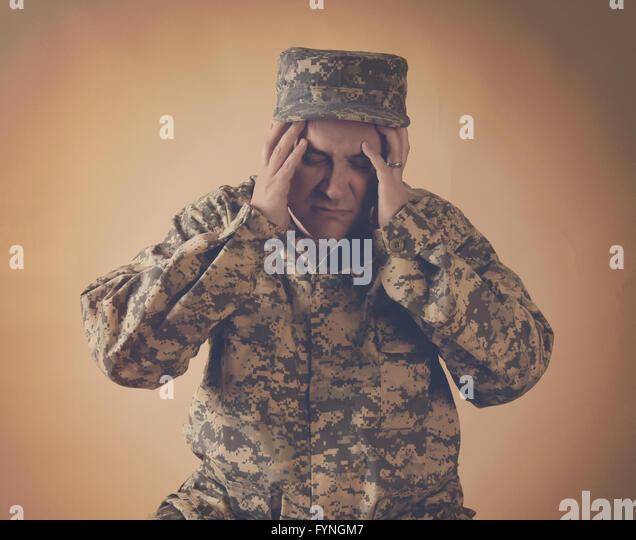 A stressed army man is holding his hands to his head on an  isolated background for a war effect or pain concept - Stock Image