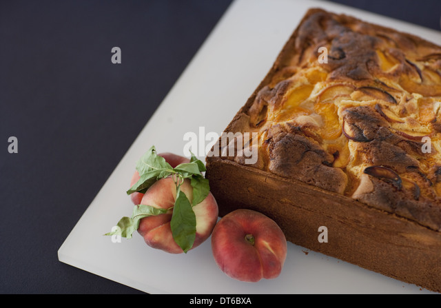 A square baked peach cake on a board with fresh peaches. Fruits. Organic fresh food on a farm stand with a herb - Stock Image