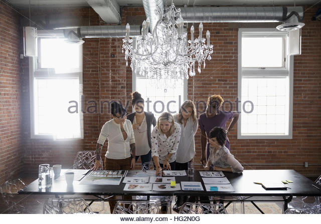 Female designers meeting and brainstorming reviewing proofs in conference room - Stock Image