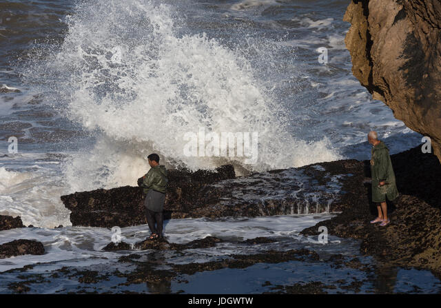 A man waits for a gap between the large Altantic waves breaking on the shoreline to gather shellfish - Stock Image