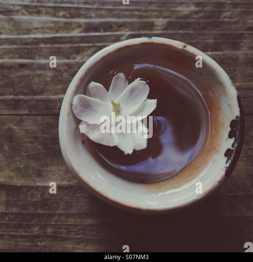 Small jasmine flower floating in tiny clay cup on wood from above. - Stock Image