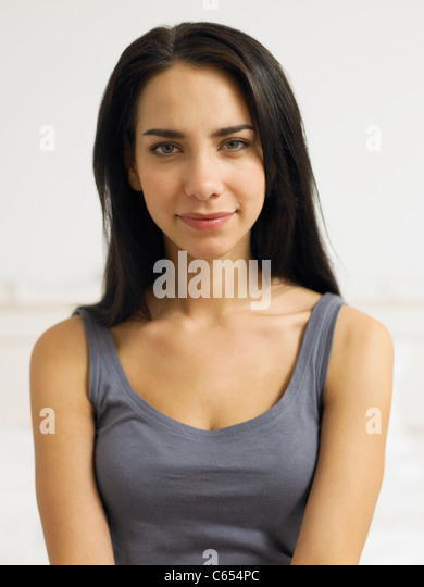 Young woman wearing grey vest, portrait - Stock Image