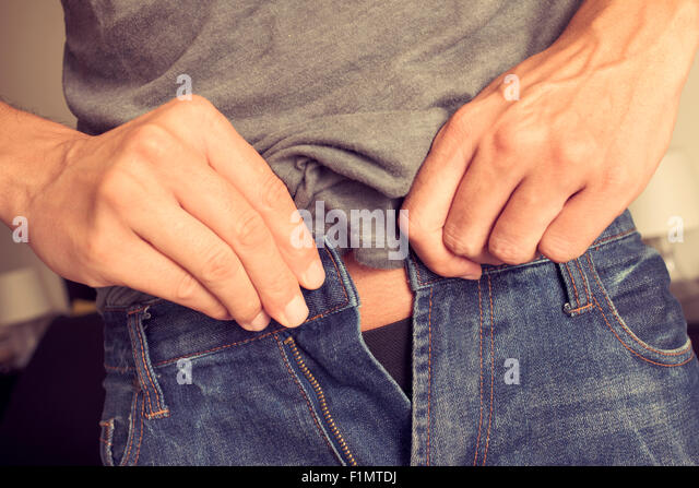 closeup of a young man trying to fasten his trousers, because of the weight gain - Stock Image