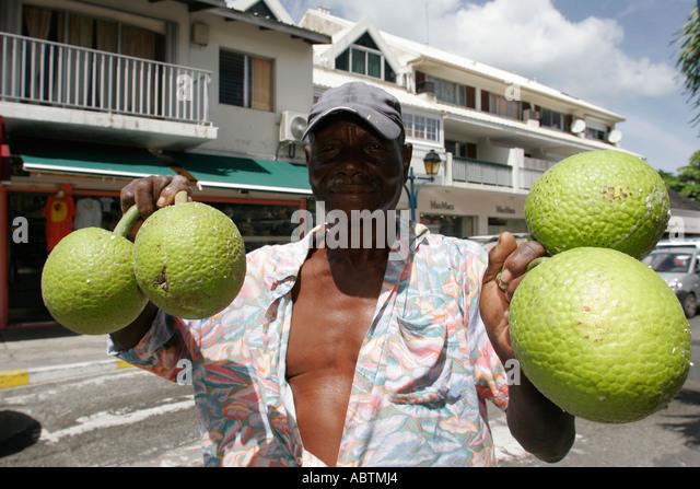 Saint Martin Marigot French Rue de President Kennedy Black male carries breadfruit - Stock Image