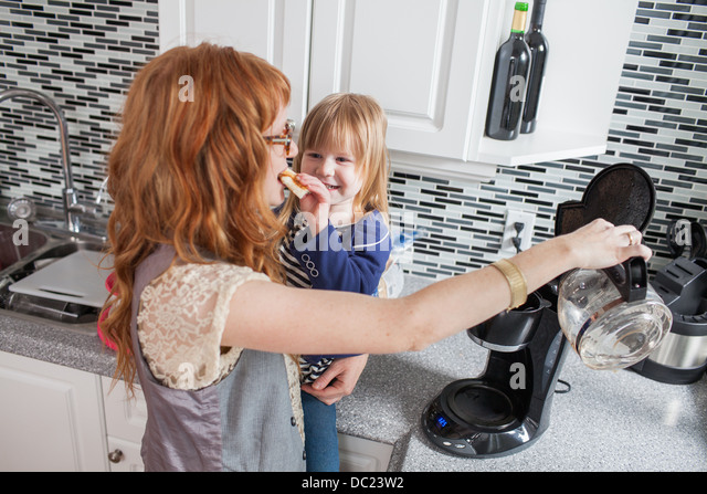 Girl feeding mother, filling coffee machine - Stock-Bilder