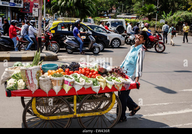 India Indian Asian Mumbai Tardeo Jehangir Boman Behram Road man cart produce vendor vegetables smiling - Stock Image