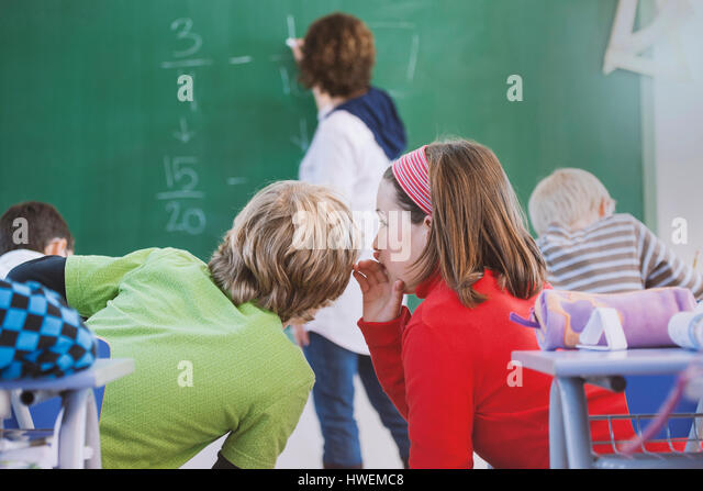 Teacher writing on blackboard, two students whispering to each other behind her - Stock-Bilder