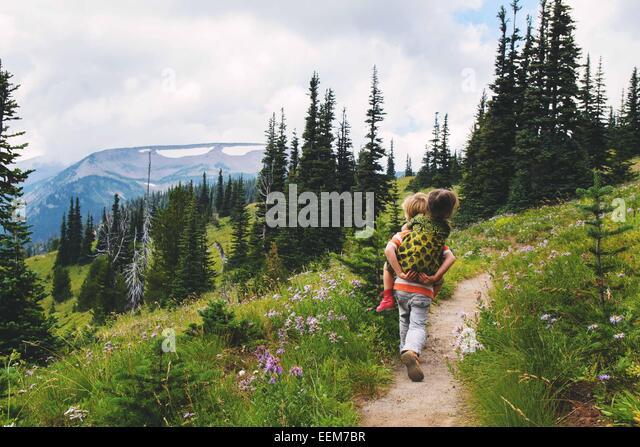 Boy (4-5) giving girl (2-3) piggyback ride along mountain trail - Stock Image