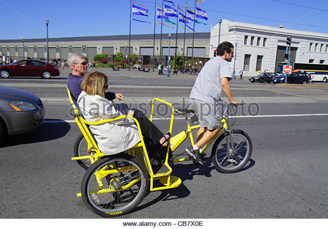 San Francisco California The Embarcadero street scene pedicab pedaling transportation man woman couple job tricycle - Stock Image