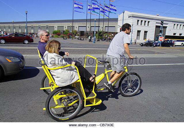 San Francisco California The Embarcadero street scene pedicab pedaling transportation man woman couple job tricycle - Stock Image