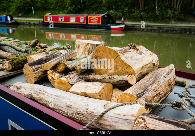 Sawn logs of wood on the roof of a narrow canal house boat - Stock Image