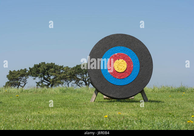 Well-used archery target with yellow bull's-eye, and numerous arrow holes. Metaphor for many business-oriented - Stock Image