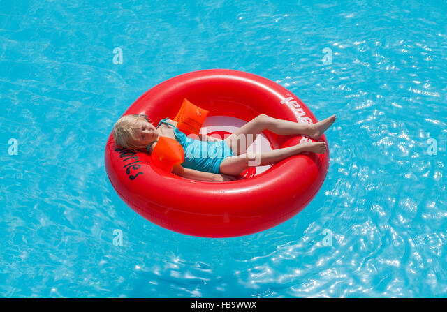 Greece, Karpathos, Amopi, Girl (6-7) lying in inflatable wheel - Stock Image