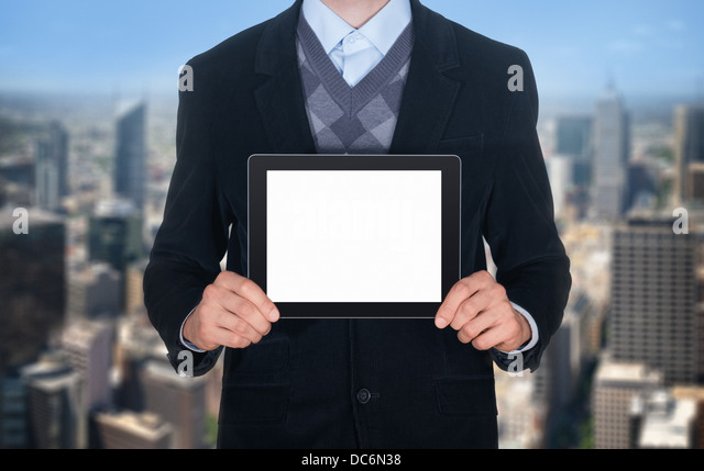 Handsome businessman in black suit showing modern digital tablet with blank screen. Isolated on cityscape background - Stock Image