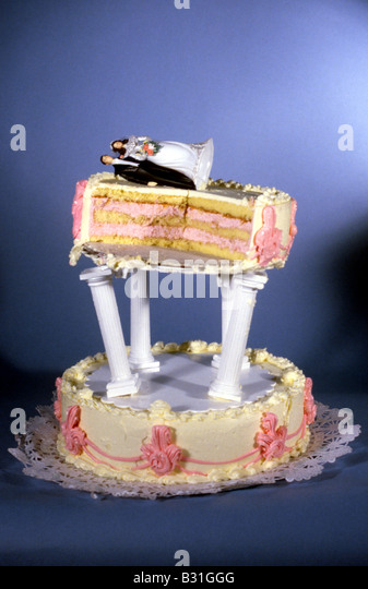 a tiered wedding cake with pieces of cake cut out and a toppled ornament of bride and groom - Stock-Bilder