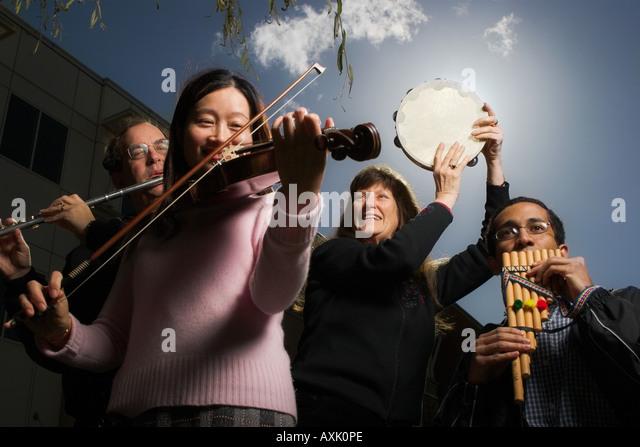 people man ladies women men violin tambourine flute music sound sky listen happy joy celebration event blue pink - Stock Image