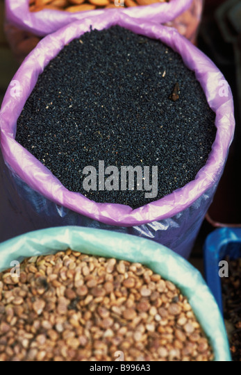Nigella seeds and lentils in buckets, high angle view - Stock Image