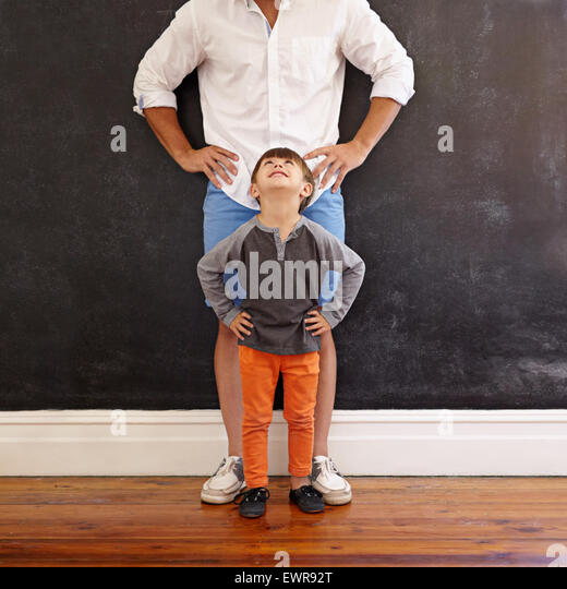 Indoor shot of little boy looking at his father while standing in front with hands on waist. - Stock Image