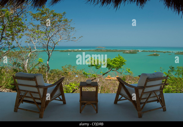 Two chairs over vivid green Caribbean water - Stock Image