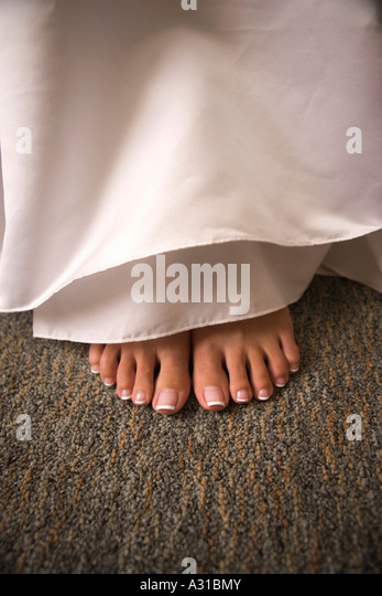 Pedicured feet below dress - Stock-Bilder