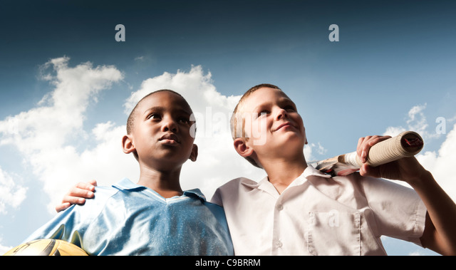 Two boys holding cricket bat and ball outdoors, Johannesburg, Gauteng Province, South Africa - Stock Image