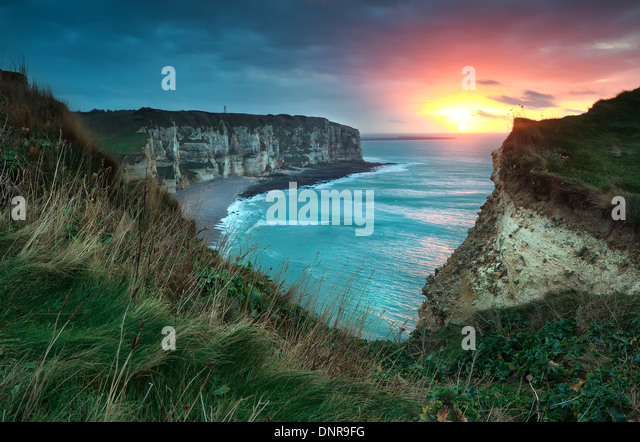 warm sunset over cliffs and ocean, Etretat, France - Stock Image