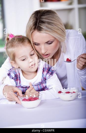woman and girl with yogurt bowl - Stock Image