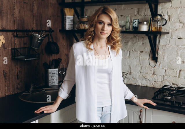Portrait of serious Middle Eastern woman standing in domestic kitchen - Stock-Bilder